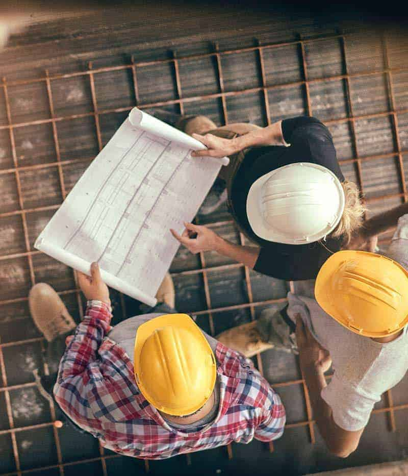 overhead photo of three people in hard hats looking at blueprints