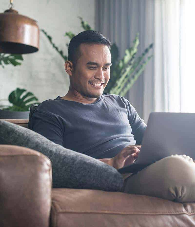 photo of smiling man sitting on leather chair and working on laptop
