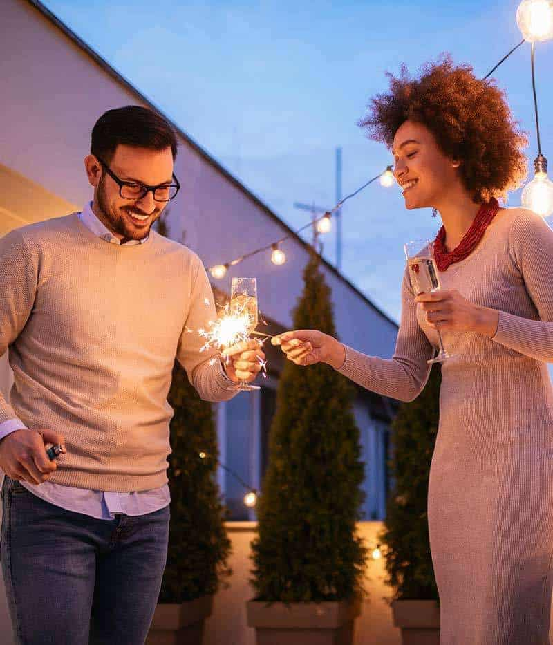 photo of man and woman holding sparklers and wine glasses